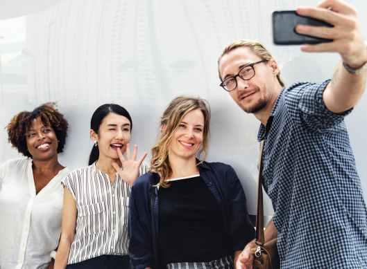 three smiling women beside man holding smartphone
